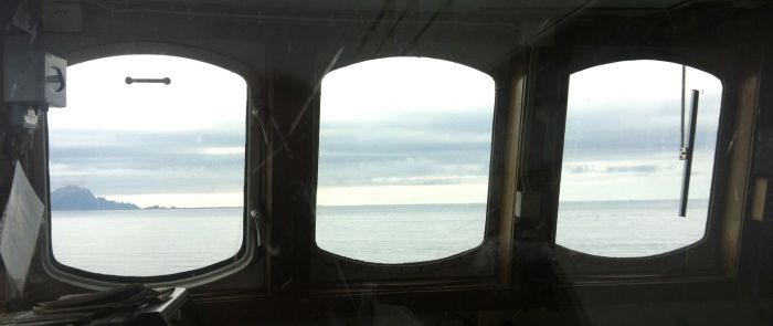 Målet flimrer i det fjerne, gjennom Gryllefjordferjas velsalta vindusglass.