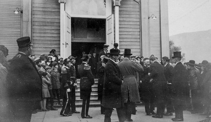 Adolf Hoel spankulerer forbi inngangen til domkirka i Tromsø sentrum etter minnegudstejenesten den 8. september 1930. Litt til høyre sees Biskop Eivind Berggrav som kondolerer Ebbe Andrée. (Fra Perspektivet Museums Flickr-konto)